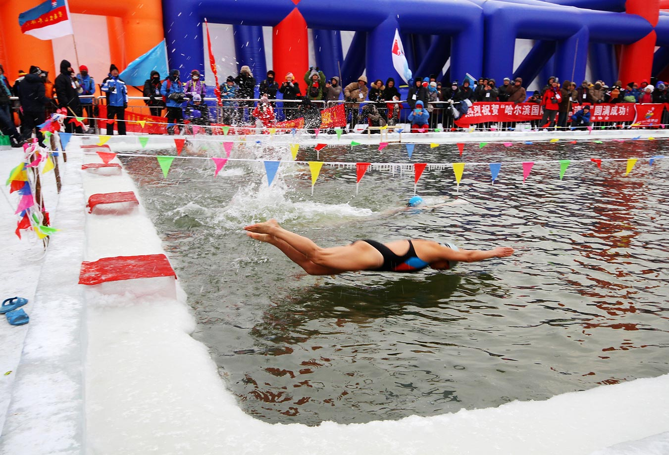 A swimmer dives into a pool during the 16th Harbin International Ice and Snow Festival in Harbin, Heilongjiang province of China.