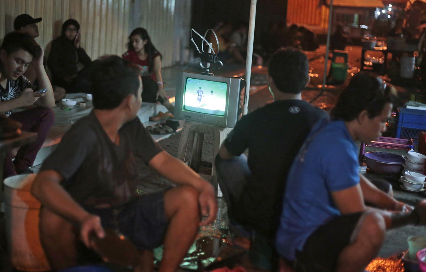 Indonesians watch at a road-side food stall in Surabaya, East Java, Indonesia.