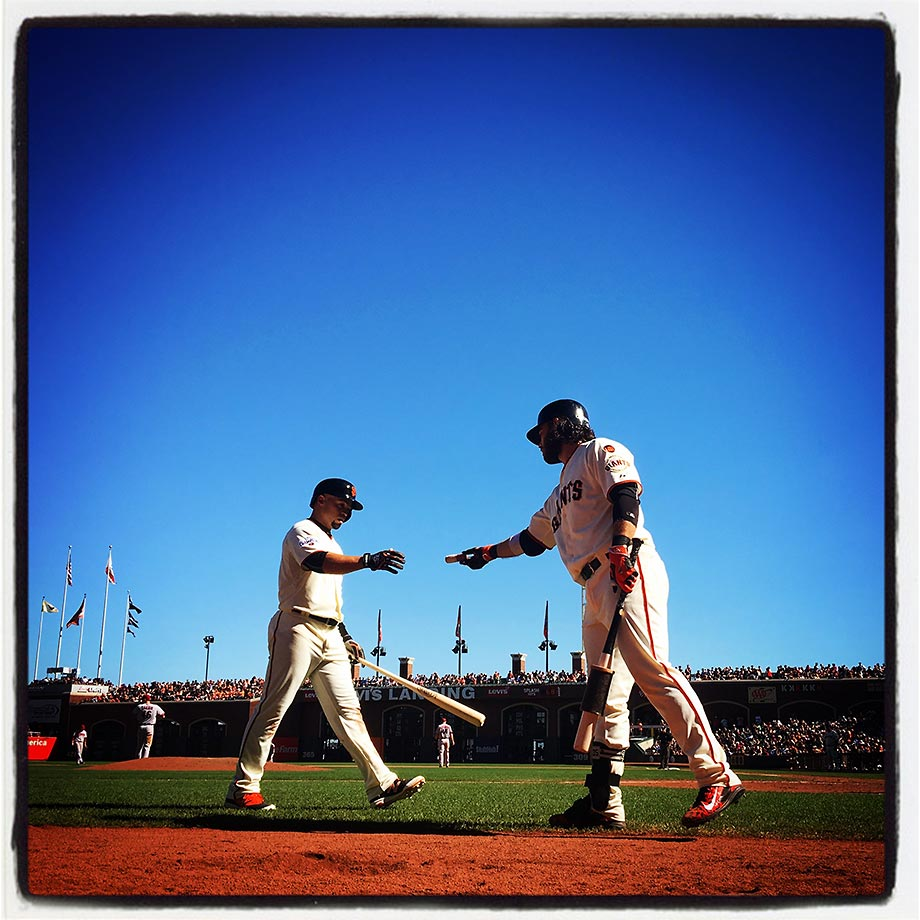 Brandon Crawford of the San Francisco Giants hands a Mota Stick to teammate Juan Perez in the on-deck circle during a game against the Arizona Diamondbacks at AT&T Park in San Francisco on Saturday, Sept. 19, 2015.