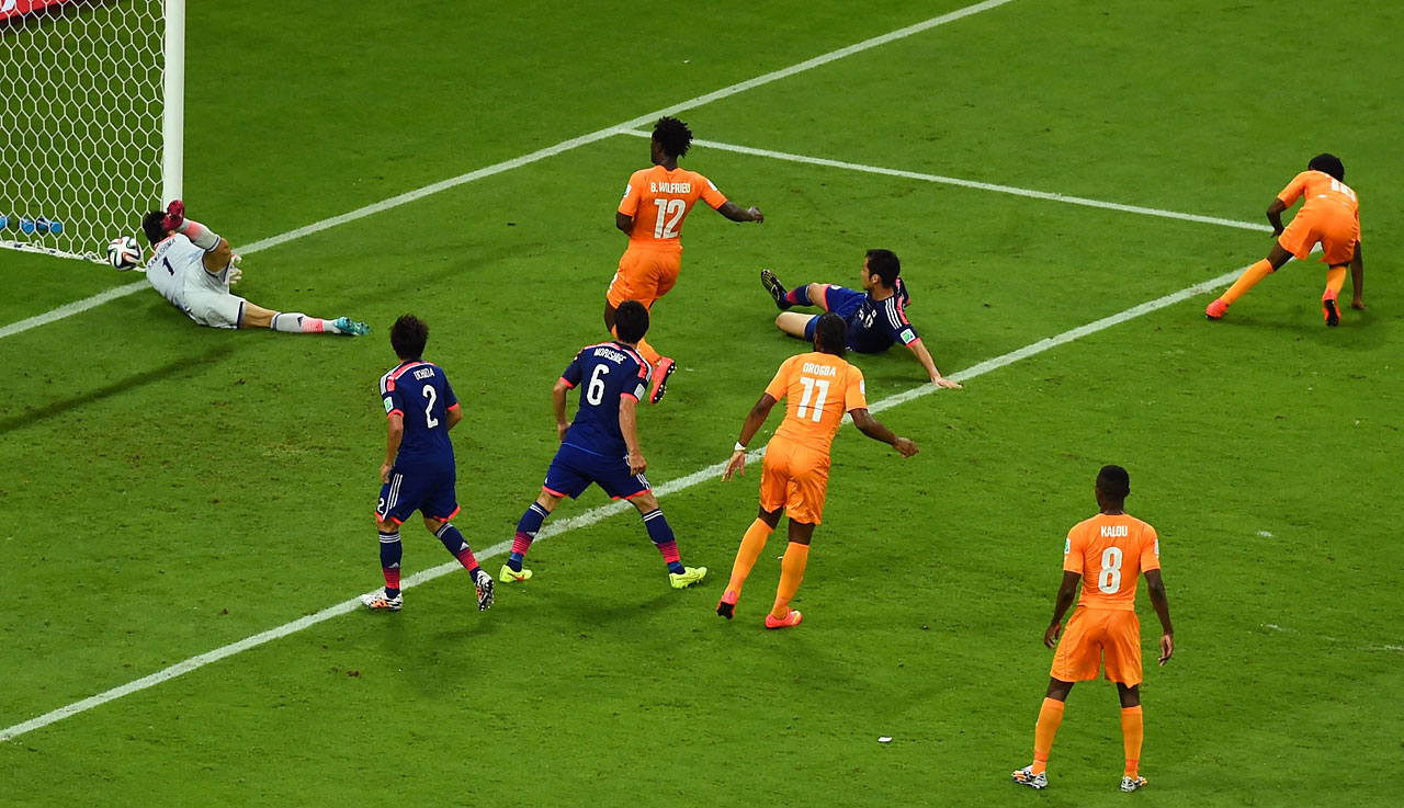 Gervinho of the Ivory Coast (right) scores his team's second goal on a header past goalkeeper Eiji Kawashima of Japan.