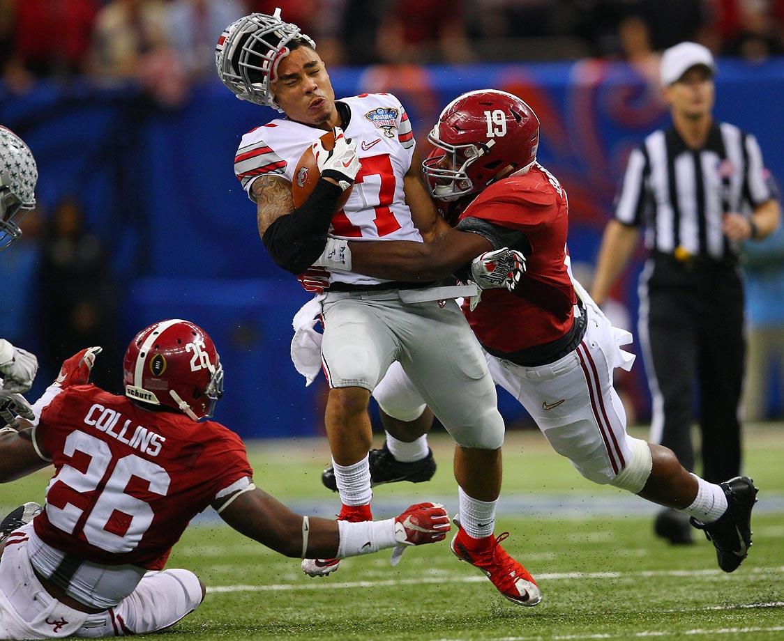 Jalin Marshall of Ohio State loses his helmet against Reggie Ragland of Alabama.