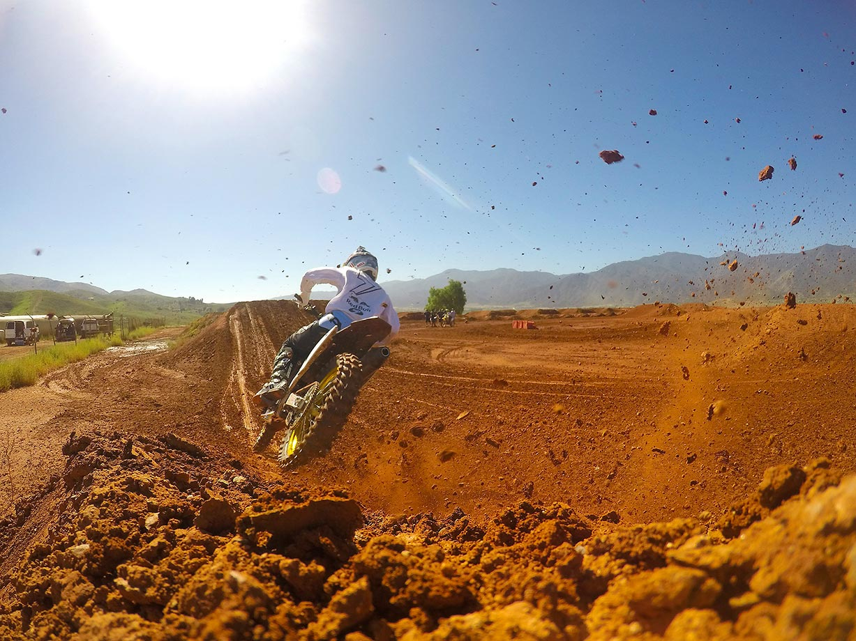 Dirt and mud fly as Suzuki supercross rider James Stewart comes out of a turn during a practice run.