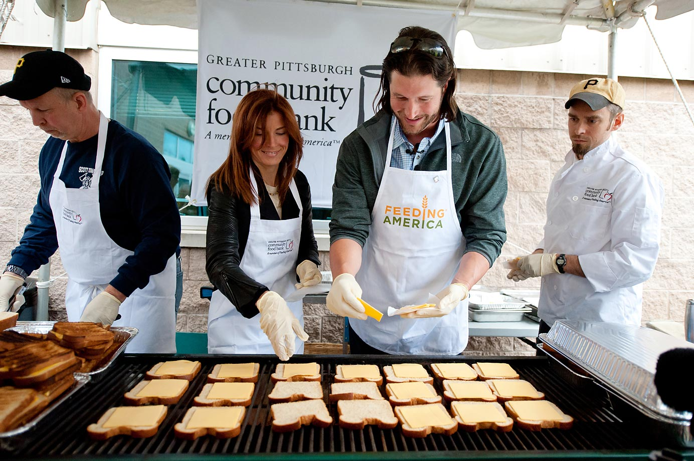 Pittsburgh Pirates pitcher Jason Grilli and his wife volunteer at the Greater Pittsburgh Community Food Bank by serving grilled cheese sandwiches to Pittsburgh area food bank clients.