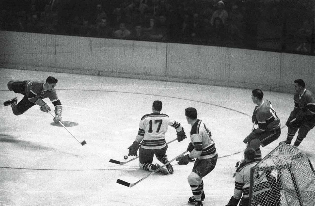 Jean Béliveau flies through the air while shooting the puck against the New York Rangers at Madison Square Garden on Nov. 20, 1955.