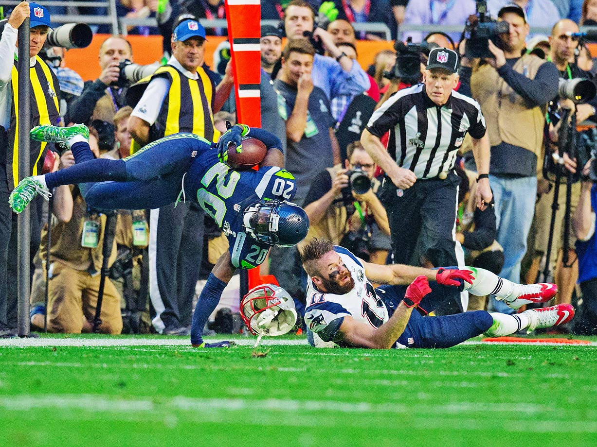 Jeremy Lane of the Seattle Seahawks is tackled by Julian Edelman after making an interception in the first quarter of the Super Bowl.