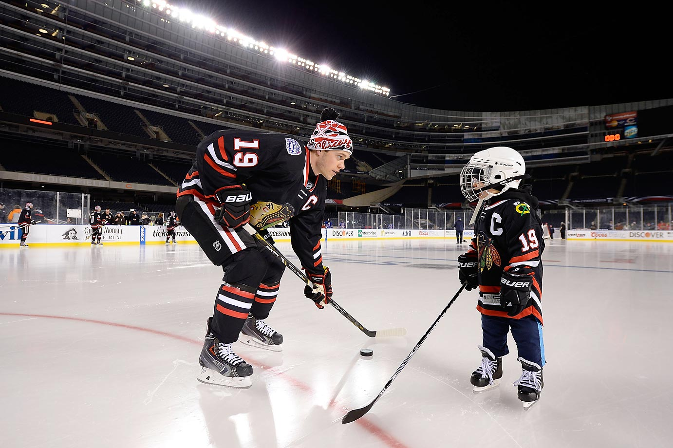 Jonathan Toews of the Chicago Blackhawks skates with 4-year-old Make-A-Wish guest Nicholas Skretkowski during the NHL Stadium Series family skate at Soldier Field.
