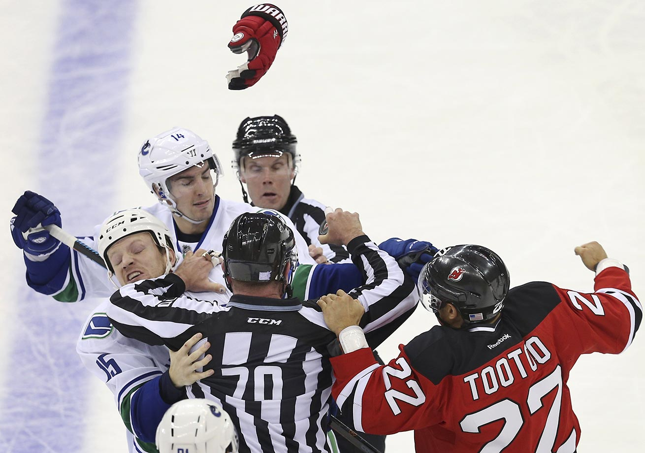 Jordin Tootoo of the New Jersey Devils fights with Alexandre Burrows and Derek Dorsett of the Vancouver Canucks. The Devils won in overtime 4-3.