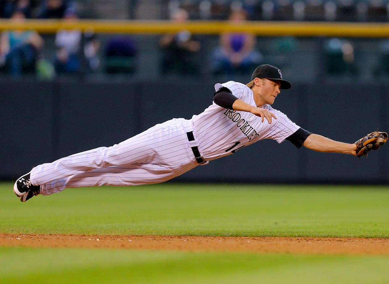 Shortstop Josh Rutledge of the Colorado Rockies makes a diving catch for the first out of the third inning in a game against the Padres.