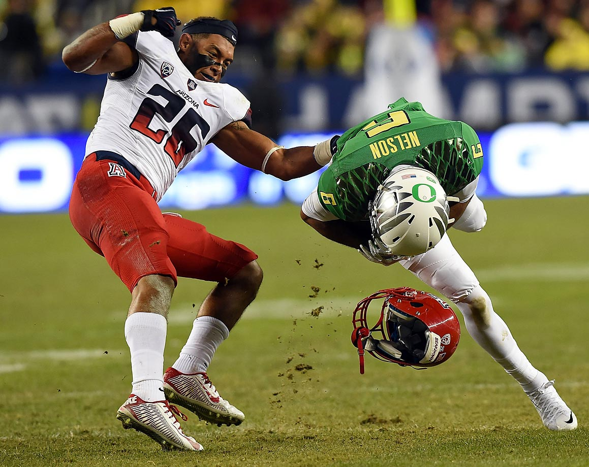 Jourdon Grandon of Arizona loses his helmet while defending Charles Nelson of Oregon.