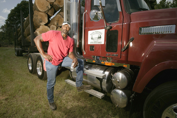 Malone poses outside one of the tractor trailer he drives for his logging company Malone Properties Timber Company in 2003. (Bill Frakes/SI)