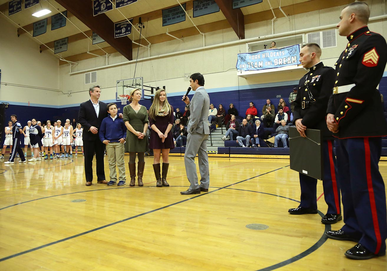 Flanked by representatives of the U.S. Marine Corps, SI managing editor Chris Stone (in gray) addresses Kate and her family at center-court