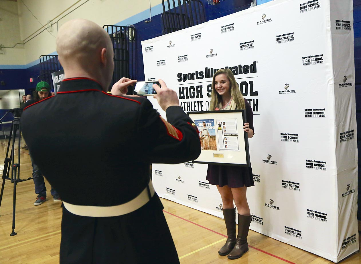 Kate poses with her framed SI issue for a U.S. Marine Corps photographer.