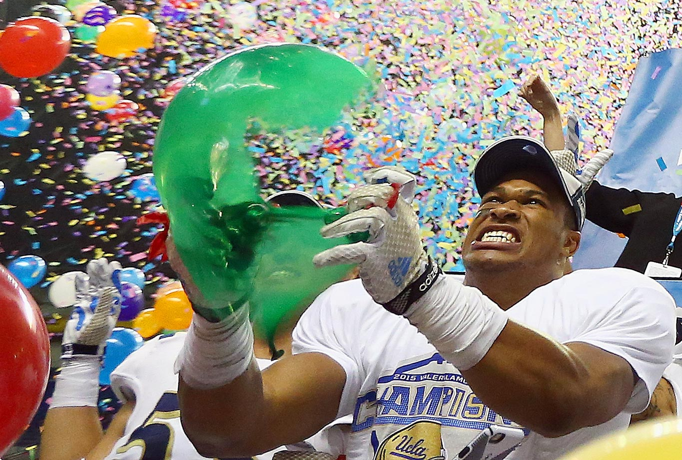 Kenny Young of UCLA pops a balloon after their 40-35 win against Kansas State in the Valero Alamo Bowl.