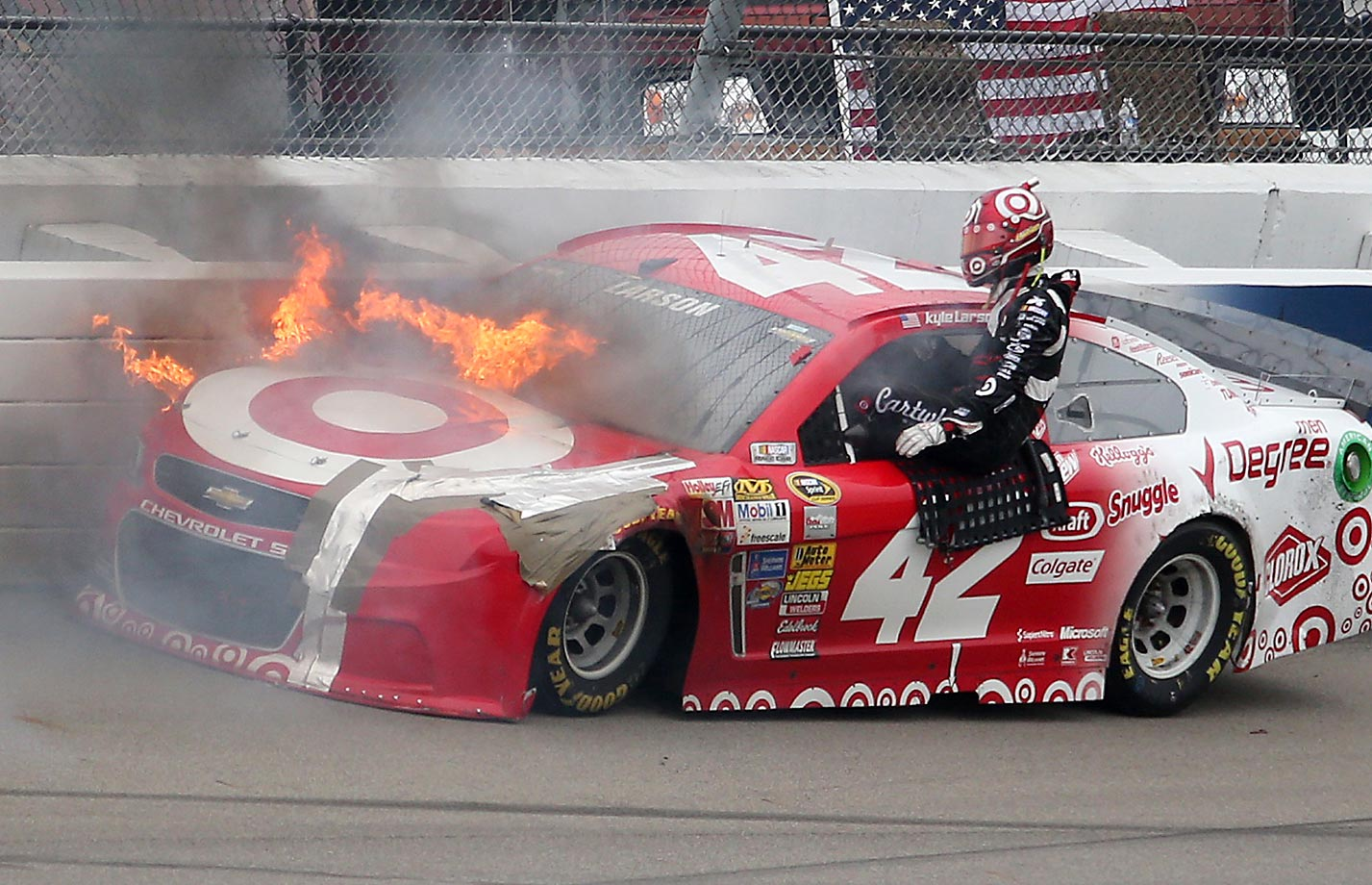 Kyle Larson quickly exits his car after it caught fire in a crash off Turn 4 of the NASCAR Sprint Cup Series Pure Michigan 400.