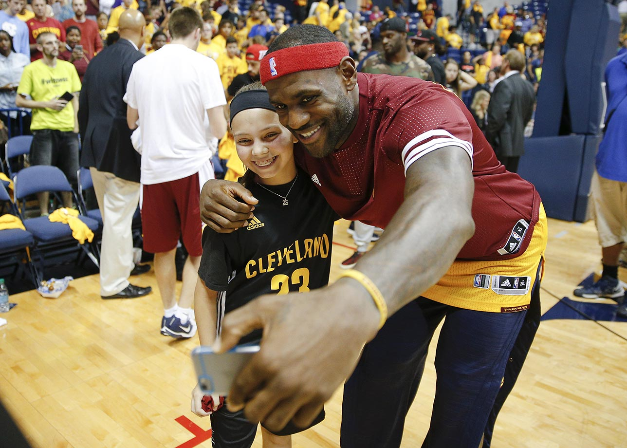 LeBron James takes a selfie with a young fan after an NBA preseason basketball game against the Atlanta Hawks.