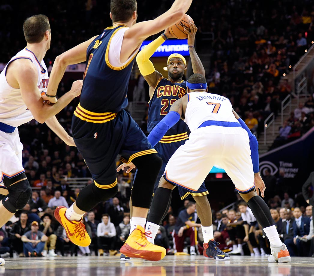 LeBron James, guarded by Carmelo Anthony, looks to pass in the Cavaliers' season-opening 95-90 loss to the Knicks.