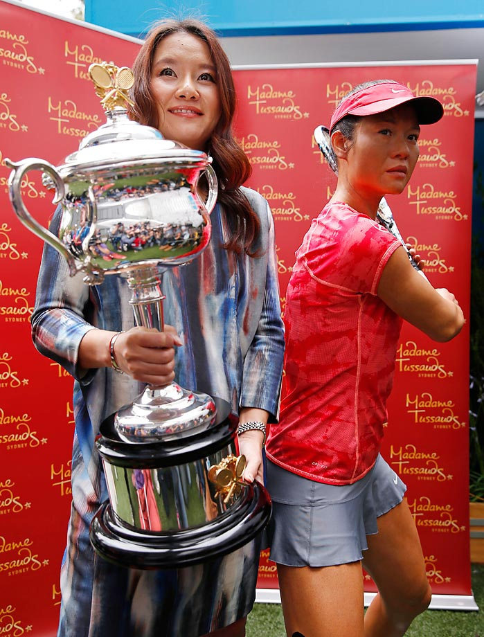 Defending Australian Open champion Li Na of China holds the singles trophy next to her wax model.