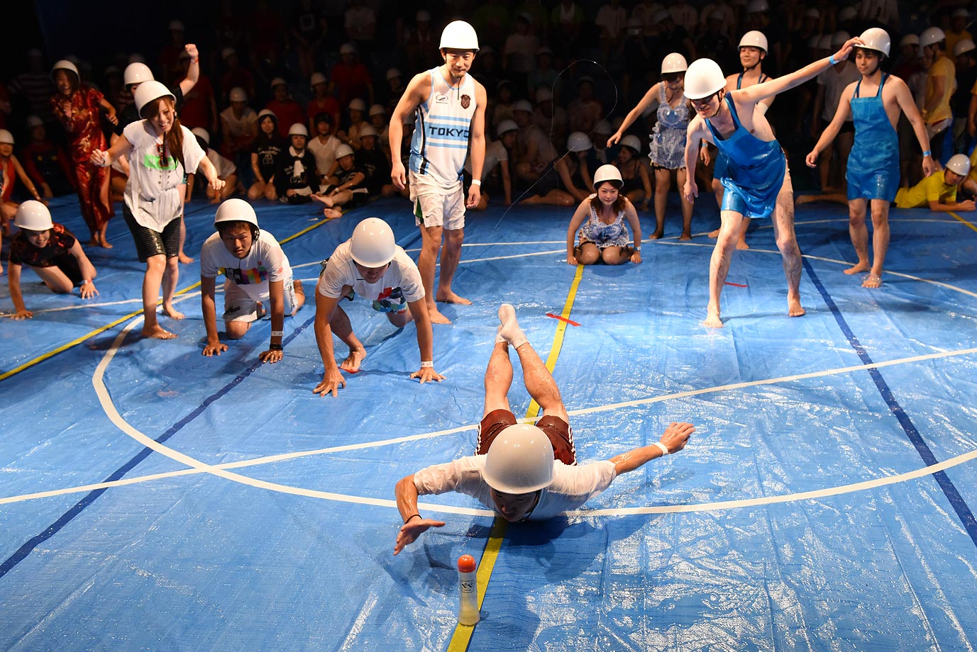Contestants rush to catch a plastic bottle as they compete in the 'Lube Olympics' in Tokyo.