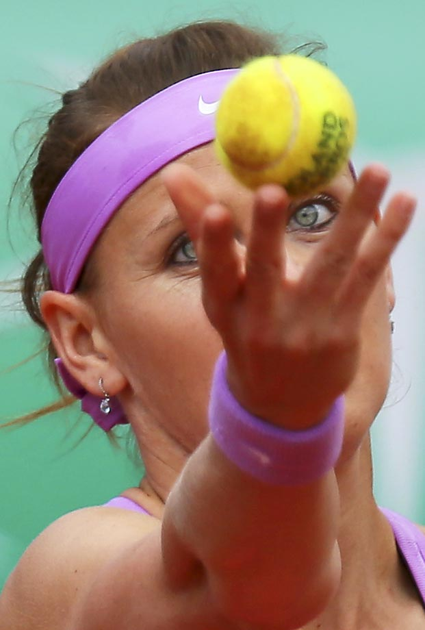 Lucie Safarova serves against Garbine Muguruza at the French Open.