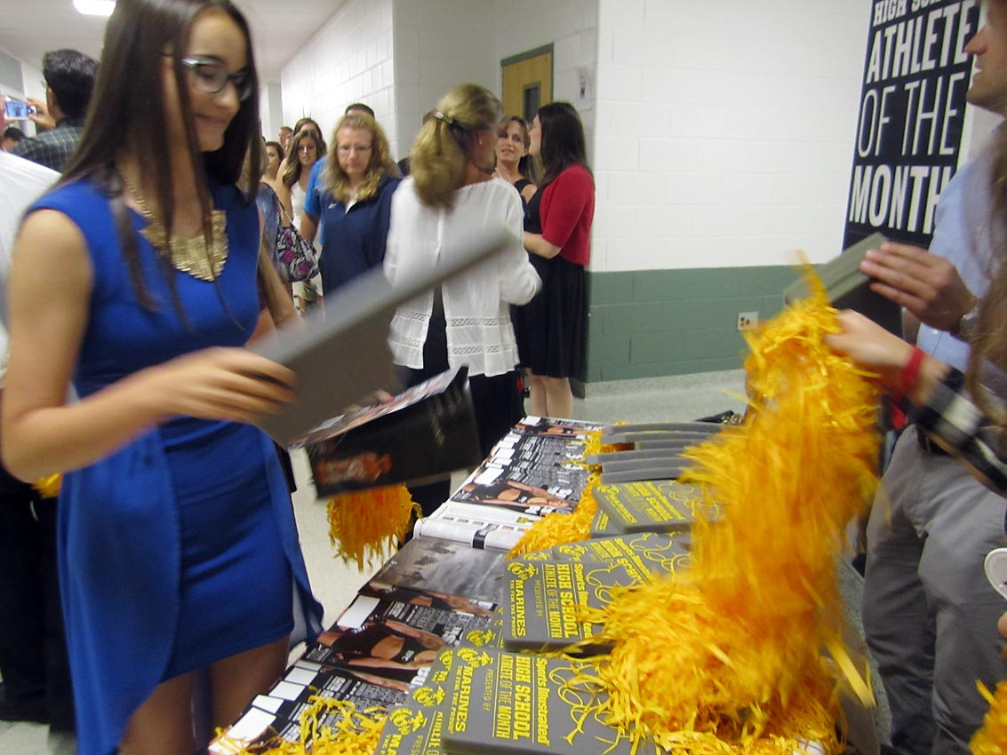SI was on hand to give out free pom-poms, foam fingers and copies of Sports Illustrated to student-athlete and their families.