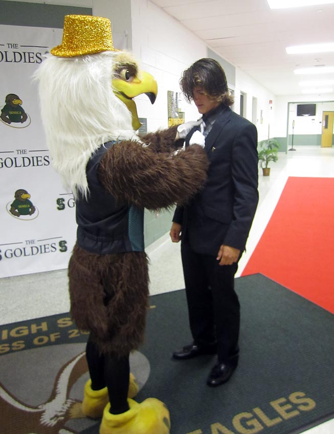 The Seneca High mascot helps a fellow student tie his tie.
