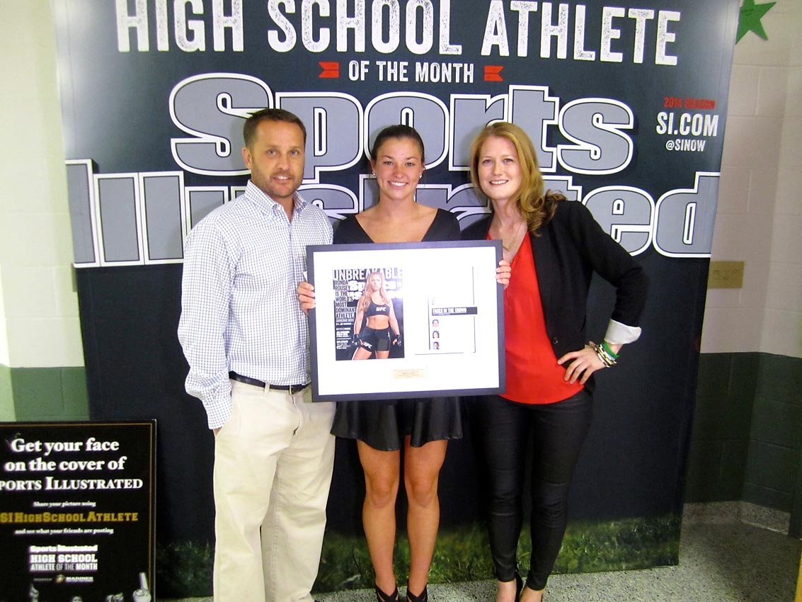 Mark Millon, a former Major League Lacrosse MVP, two-time member of Team USA and National Lacrosse Hall of Famer poses Maddy (center) and SI editor Ali Fenwick, as Maddy shows off a framed commemorative copy of her debut in the pages of SI.
