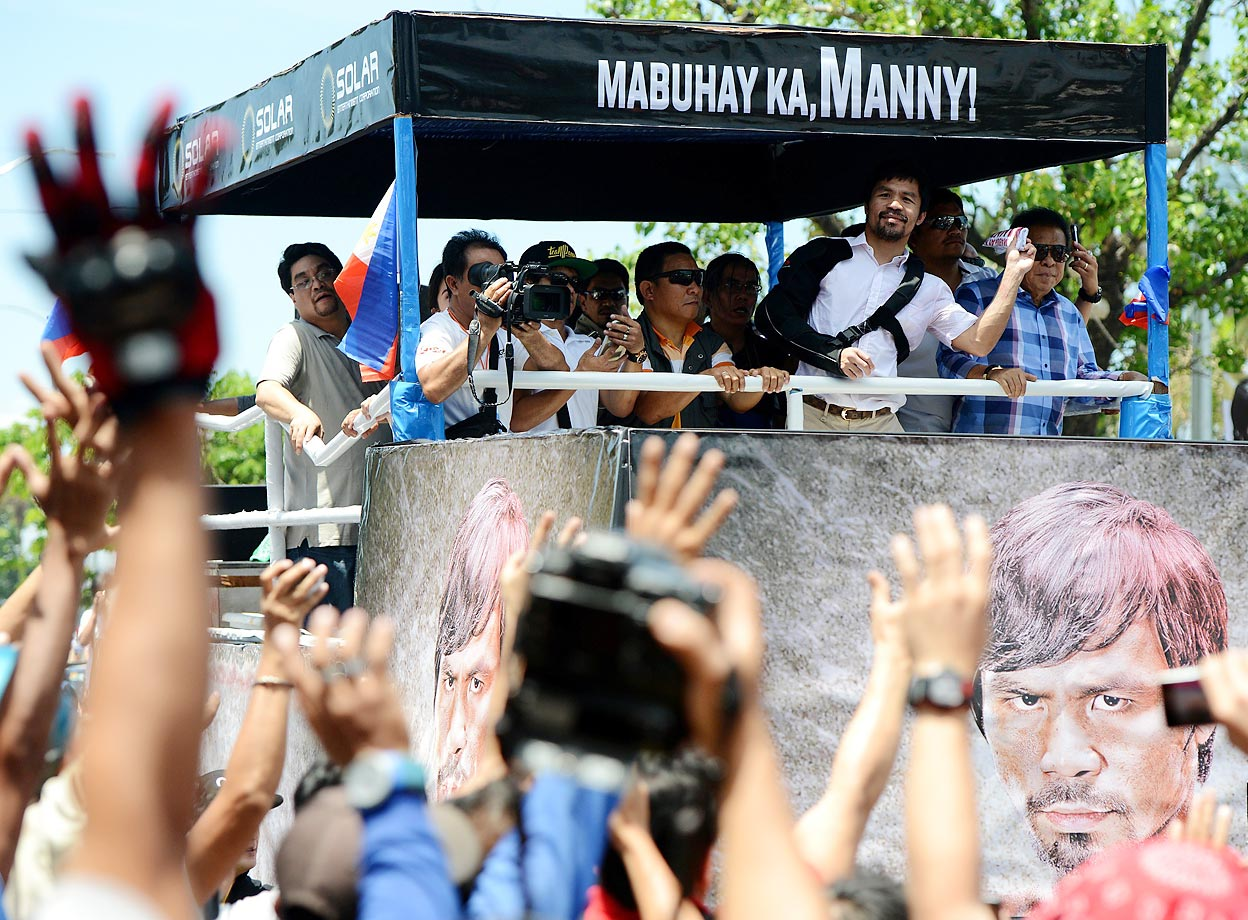 Manny Pacquiao throws a shirt to fans in Manila during a parade welcoming him back to the Philippines.