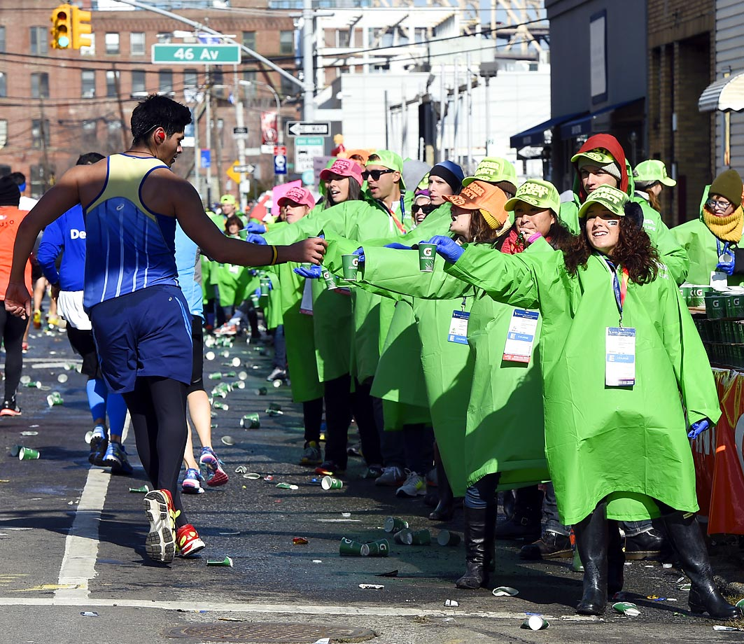 Runners pass by the water station on Vernon Boulevard. in Long Island City during the New York Marathon.