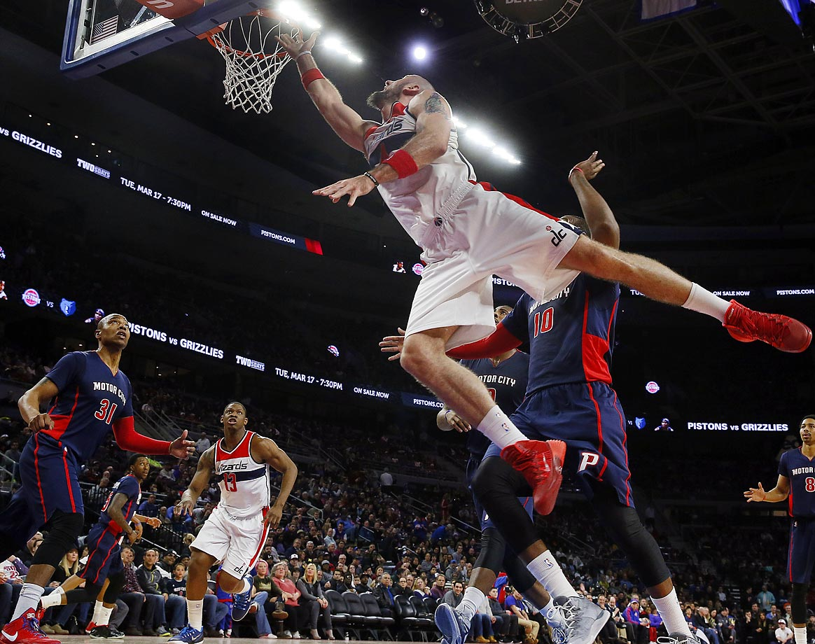 Washington Wizards center Marcin Gortat, foreground, drives against the Detroit Pistons in the second half of the Wizards-Pistons game.