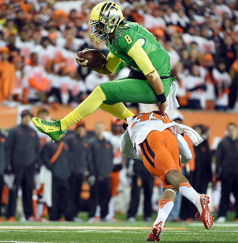 Oregon Ducks quarterback Marcus Mariota hurdles over Oregon State Beavers safety Justin Strong. The Ducks won 47-19.