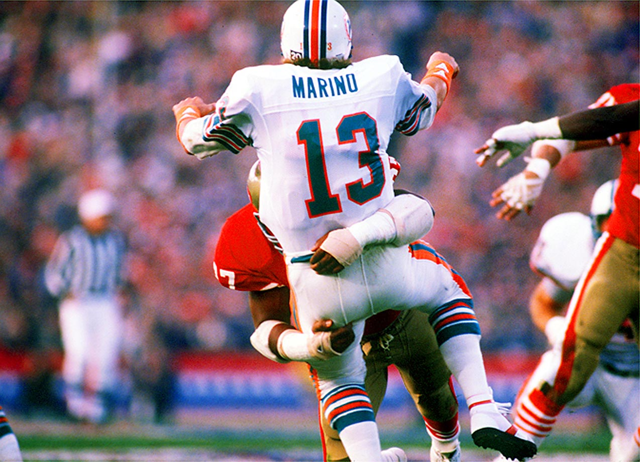 Dan Marino absorbs a big hit from San Francisco 49ers defensive tackle Gary Johnson in Super Bowl XIX, in 1985.