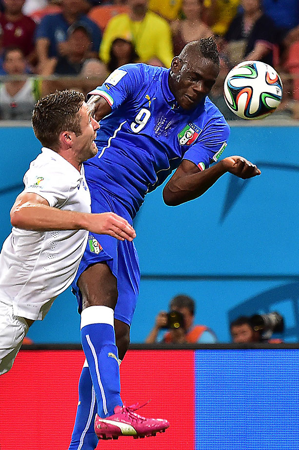 Italy's forward Mario Balotelli heads the ball to score the winning goal as England's defender Gary Cahill defends during Italy's 2-1 victory at the Amazonia Arena in Manau.