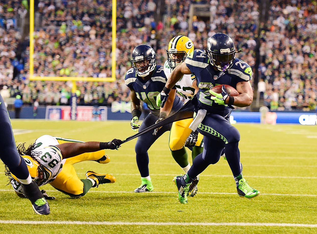Marshawn Lynch scores his second touchdown, this time with Josh Boyd and Nick Perry of the Packers trying in vain to stop him.