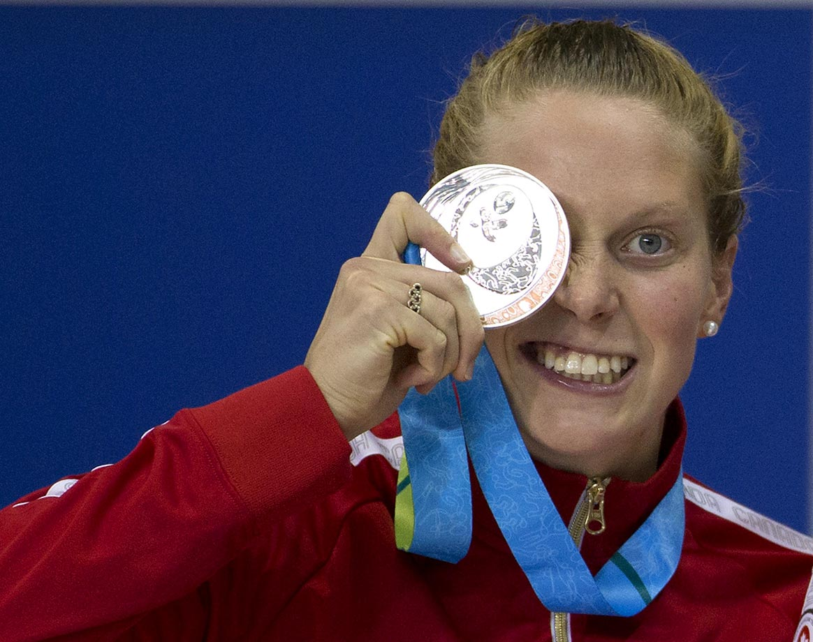 Martha McCabe jokes around with her silver medal for the 200m breaststroke at the Pan Am Games.