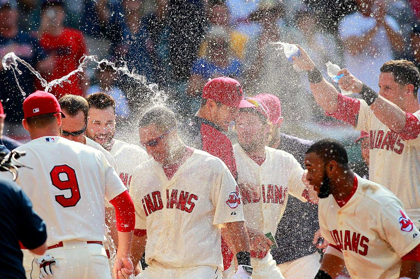 Cleveland Indians' Michael Brantley is hit with water from teammates as he reaches home plate after hitting a game-winning home run in the 12th inning of a baseball game against the Texas Rangers, Sunday Aug. 3, 2014, in Cleveland. The Indians won the game 4-3.