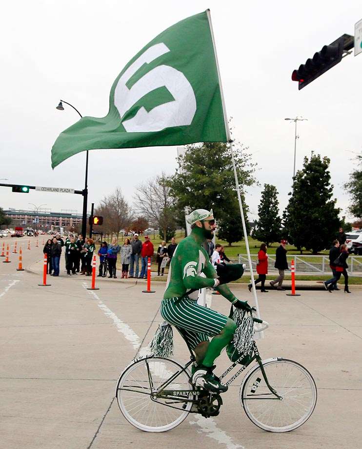 A Michigan State fan rides around AT&T Stadium before the Cotton Bowl.