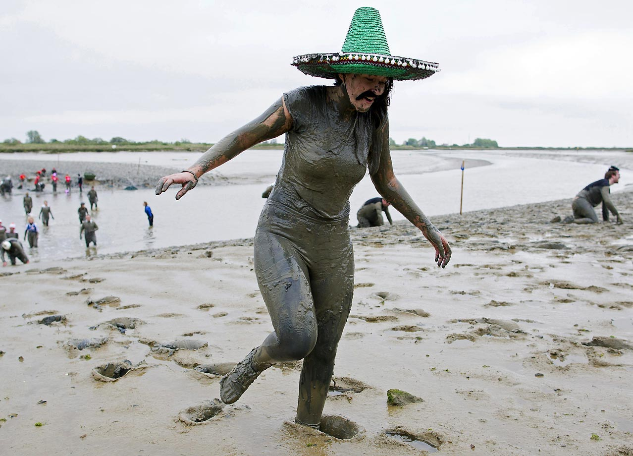 Another sombrero wearer wades through the mud and crosses the finish line during the annual Maldon Mud Race in England.