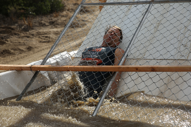 Murphy slides into icy water in a revamped version of Tough Mudder's classic obstacle, Arctic Enema.