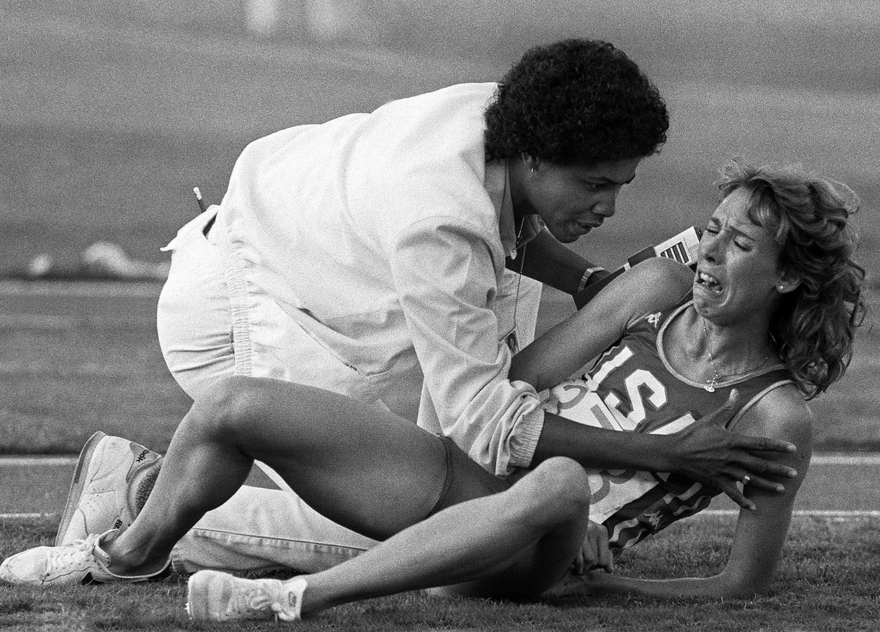 1984 Olympics | World champion Mary Decker, who became tangled with Britain's Zola Budd about halfway through the 3,000-meter run, looks on from the infield after falling from the track. The collision ended Decker's day and shook up Budd, who fell from the lead to seventh place.