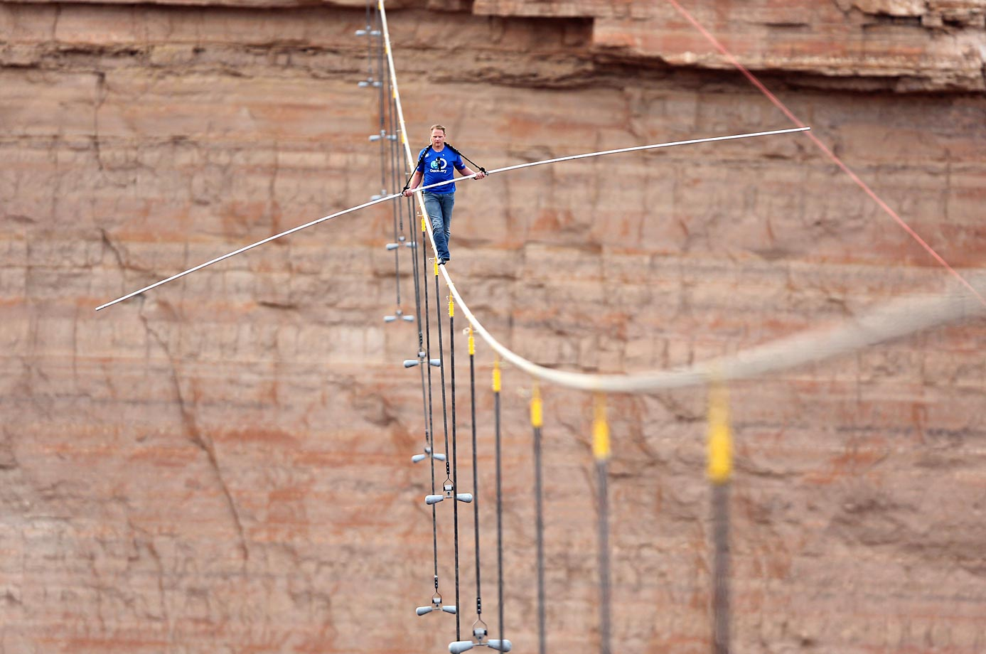 Nik Wallenda walks across a 2-inch wire 1,500 feet above the ground to cross the Grand Canyon.