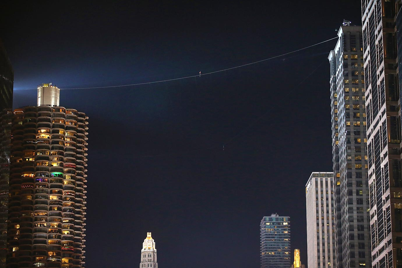 Tightrope walker Nik Wallenda (the tiny red dot you can see in the dark sky) walks from Marina City's west tower to the top of the 671-foot-tall Leo Burnett building in Chicago. The walk, which spanned 454 feet, is the highest and steepest skyscraper walk in the history of the Flying Wallenda family.