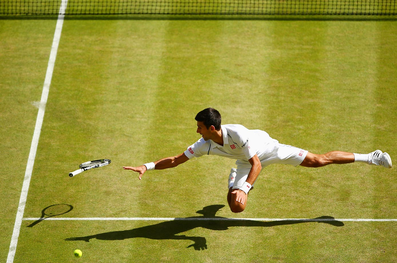 Novak Djokovic dives for a backhand against Richard Gasquet at Wimbledon.