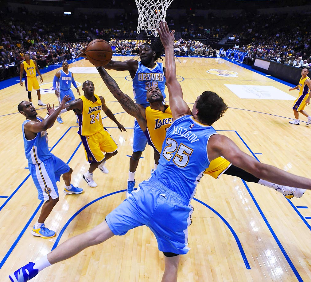 Carlos Boozer of the Los Angeles Lakers goes in for a shot with Denver's Kenneth Faried and Timofey Mozgov defending. The Lakers won the preseason game 98-95.