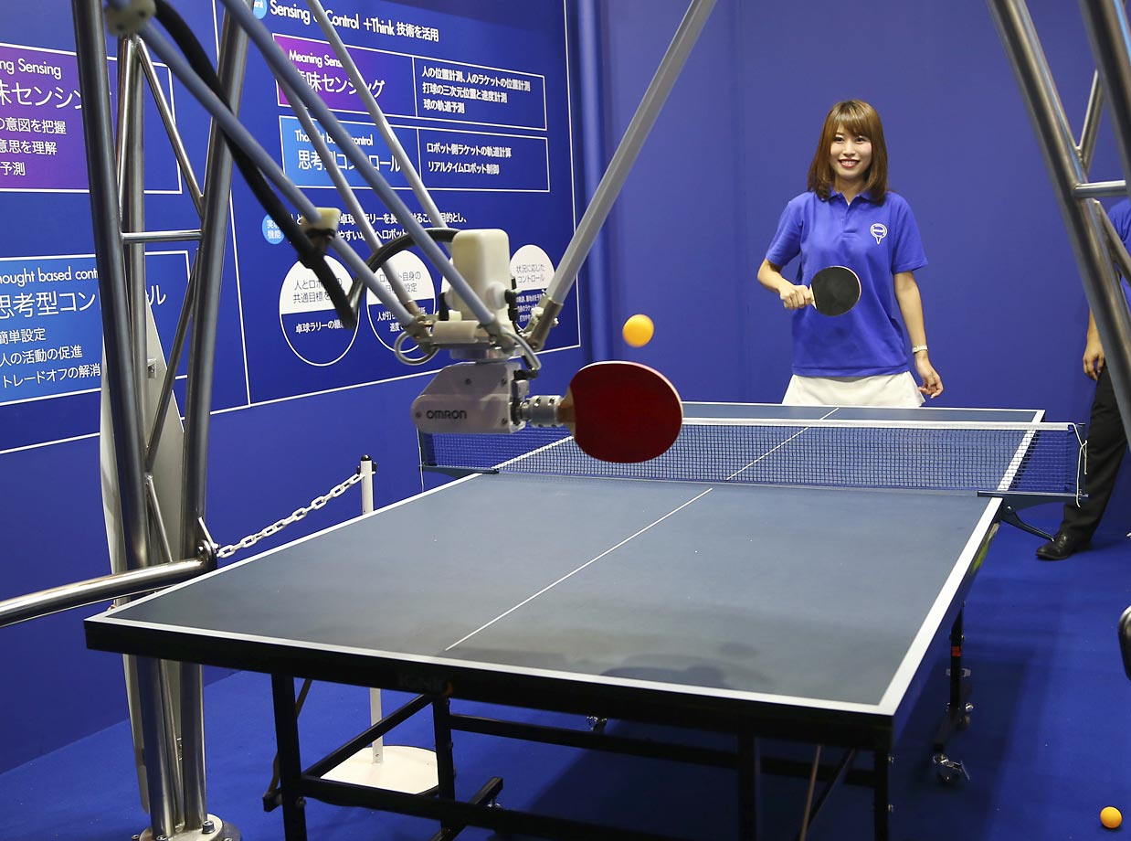 Despite its intimidating spider-like resemblance, OMRON Corp.'s three-legged robot is a relaxed ping pong playmate. With five motors to control paddle movement, it is programmed to serve the ball in a way that makes it easy for the player to return.