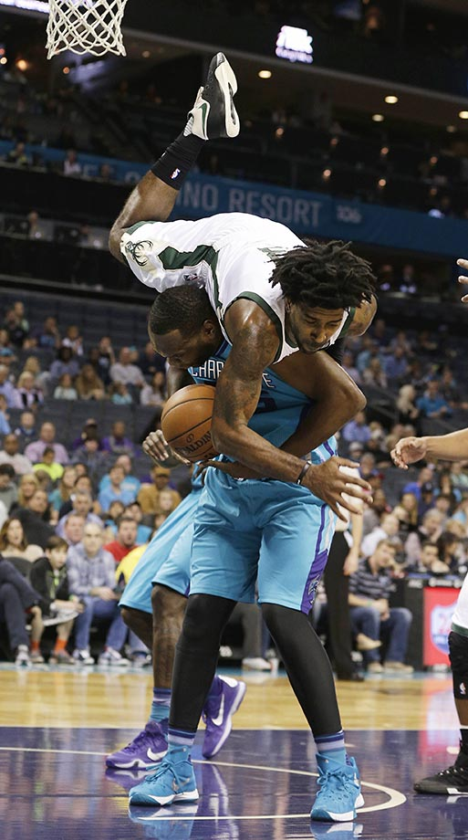 O.J. Mayo of the Milwaukee Bucks fouls Al Jefferson of the Charlotte Hornets.