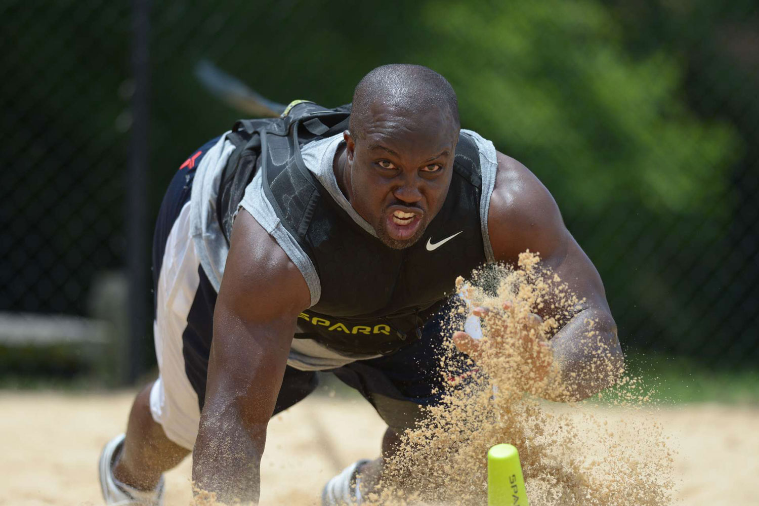 Washington Redskins linebacker London Fletcher performs the bear-crawl, sprinting in sand during a workout in June 2013.