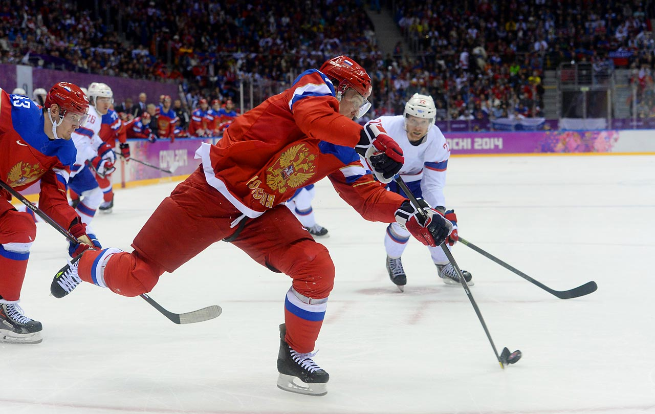 Russia's Alexei Tereshenko evades Norweigen defenders during a qualifying round Olympic hockey game. Russia won easily, 4-0.