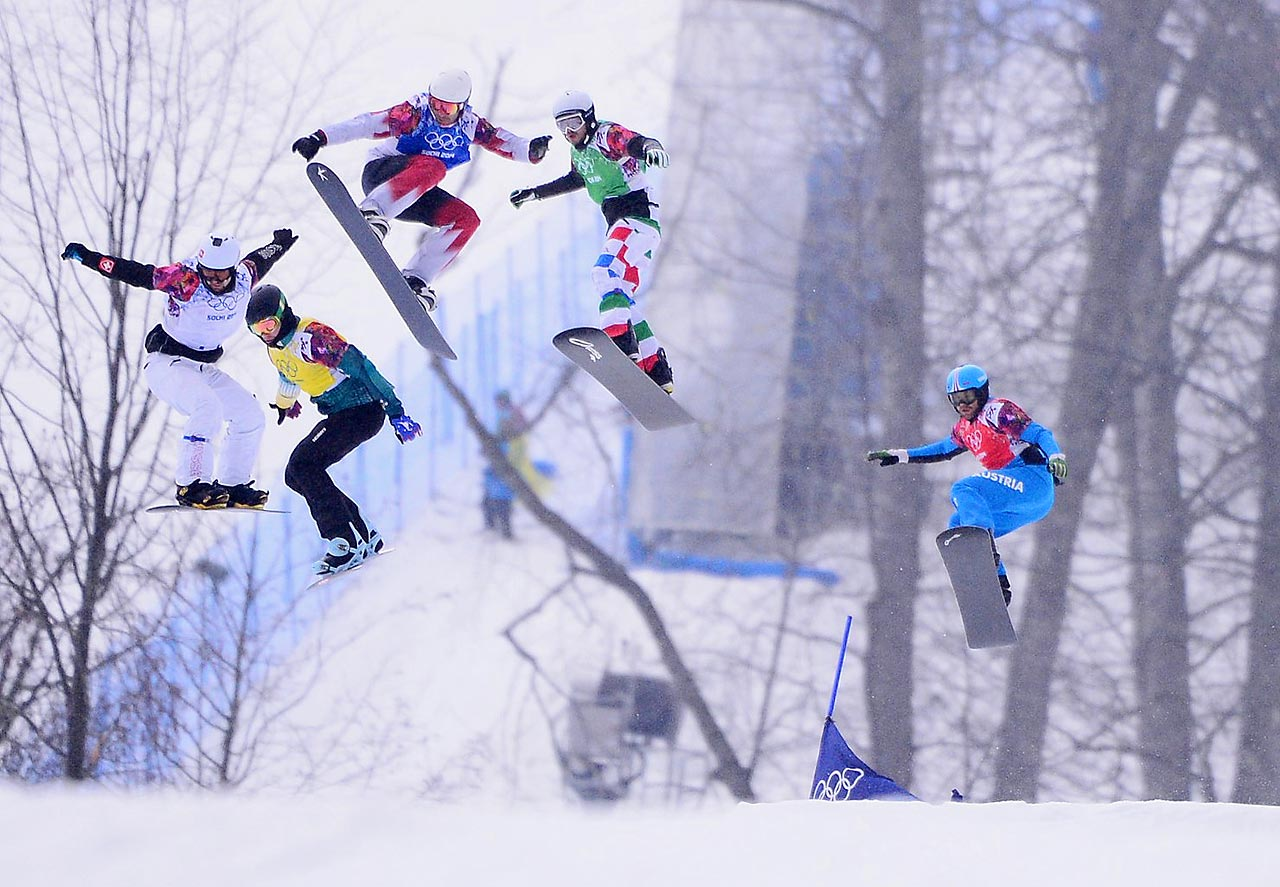 Riders take a jump during the men's snowboard cross finals.