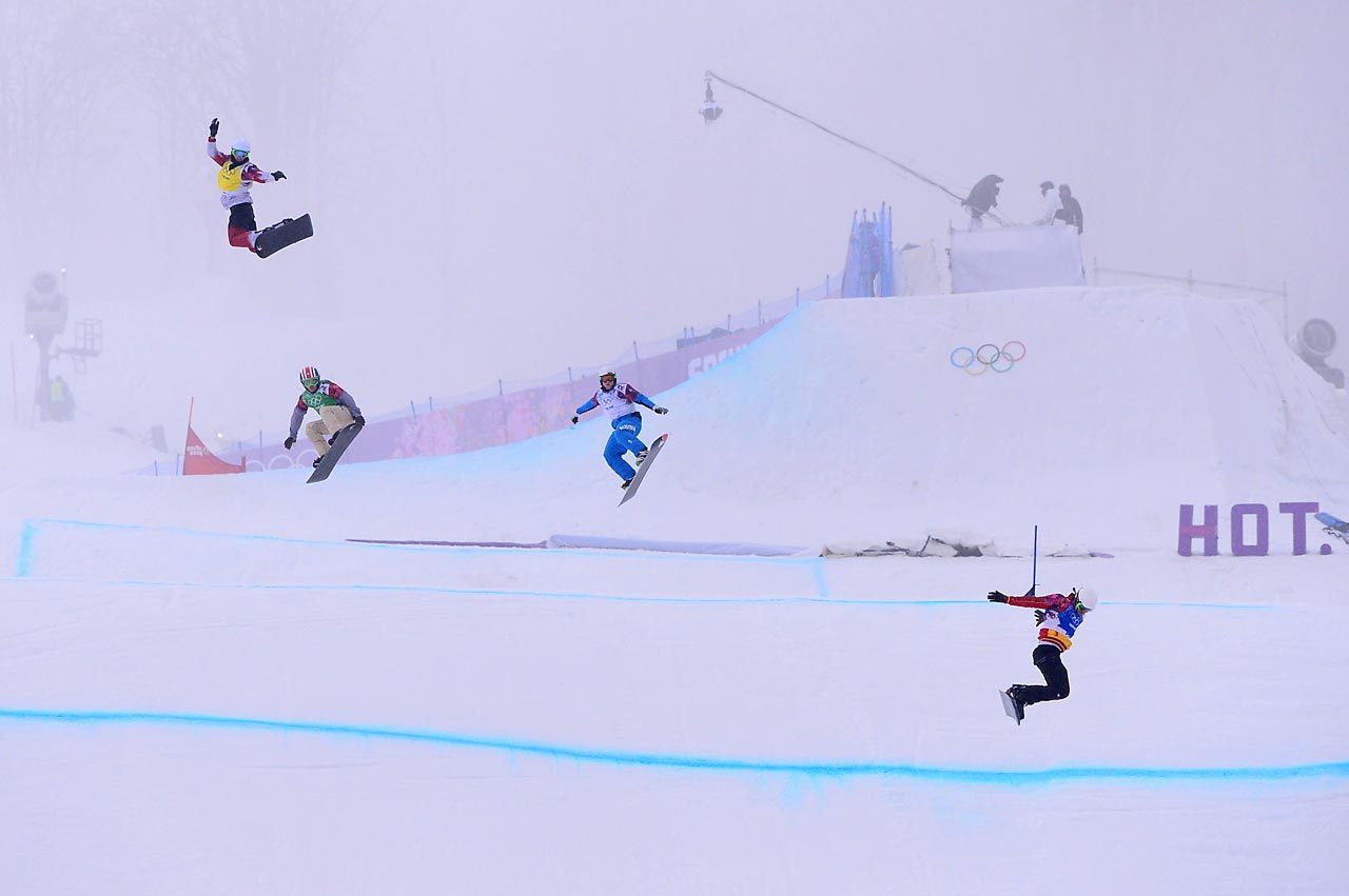 Riders jump during the small final of the men's snowboard cross competition in Sochi.
