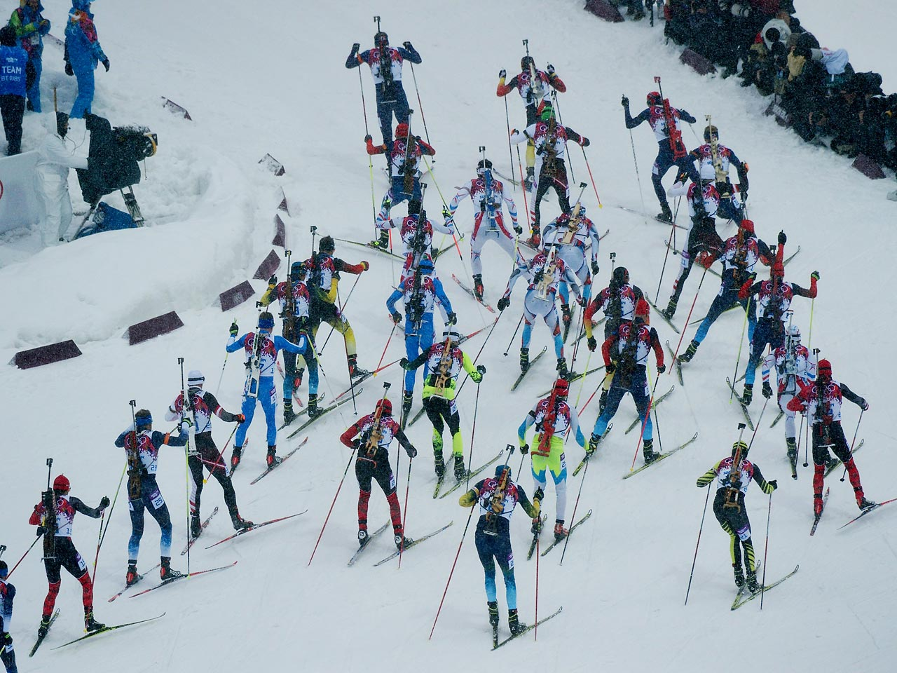 Biathlon competitors race through the course as a pack during the 15 kilometer mass start event.
